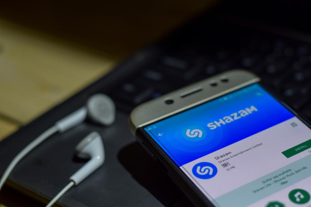 """Quante volte ti è capitato di ascoltare una canzone che ti piace e magari non conosci o ricordi il titolo o il nome dell'autore? Con Shazam ti basta cliccare un pulsante ed in pochi secondi ti dirà il nome del brano, dell'artista e l'album di riferimento. Ovunque tu sia, qualsiasi device tu stia utilizzando puoi scansionare la musica che stai ascoltando e salvarla tra le tue canzone preferite. Vediamo subito come scaricare Shazam su Android ed iOS e come utilizzare l'app anche da computer Windows e Mac. Scaricare Shazam su Android Se hai un dispositivo Android (smartphone o tablet) puoi scaricare l'app, senza pagare un solo centesimo, nel Play Store. Fai tap sull'icona (simbolo con il triangolo multicolore) e scrivi Shazam nella barra di ricerca che trovi in alto. Visualizzerai una scheda di anteprima, clicca su """"Installa"""" ed attendi la fine del download. Una volta scaricata, per utilizzare Shazam, basta cliccare su """"Apri"""". In alternativa, fai tap sull'icona di Shazam che trovi sulla tua home screen.  Scaricare Shazam su iOS Se hai un iPhone o un iPad (iOS 10.0 o versioni successive) puoi scaricare Shazam, gratuitamente, nell'App Store di iOS. Clicca sull'icona dedicata (A stilizzata su fondo azzurro), fai tap su """"Cerca"""" ed inserisci Shazam nella barra di ricerca. Una volta trovata l'app, clicca su """"Ottieni"""" e conferma l'installazione con Face ID o Touch ID o ancora inserendo la password del tuo account iCloud. Una volta scaricata ed installata l'app, per usare Shazam fai tap su """"Apri"""" o in alternativa pigia sull'icona di Shazam che trovi nella home screen del dispositivo iOS che stai utilizzando.  Come funziona Shazam  Per scoprire il titolo di un brano musicale, basta aprire l'app e cliccare sul pulsante con il logo di Shazam. Con una pressione lunga si attiva l'Auto Shazam ossia l'app resta in background e scansiona in modo automatico tutti i brani musicali che vengono riprodotti. Soltanto per il primo accesso, l'app richiede il tuo consenso per accedere al micro"""